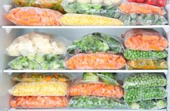 Plastic bags with deep frozen vegetables. In refrigerator stock photo
