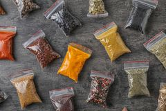 Plastic bags with different spices. On grey background, top view royalty free stock images