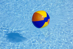 Plastic ball flying in the pool. Inflated plastic ball flying in the pool stock photo