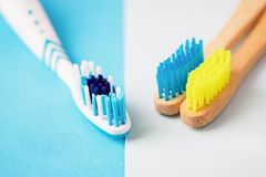 Plastic and bright bamboo toothbrushes on blue and white background. Alternative concept. Toothbrush selection, eco-friendly or. Plastic and bamboo toothbrushes royalty free stock photography