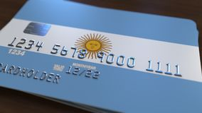Plastic bank card featuring flag of Argentina. National banking system related 3D rendering. Plastic bank card featuring state flag Royalty Free Stock Photo