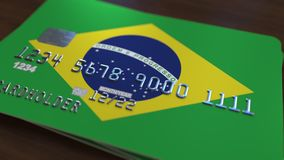 Plastic bank card featuring flag of Brazil. National banking system related 3D rendering. Plastic bank card featuring state flag Stock Photography