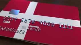 Plastic bank card featuring flag of Denmark. National banking system related 3D rendering. Plastic bank card featuring state flag Stock Photography