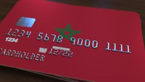 Plastic bank card featuring flag of Morocco. National banking system related 3D rendering. Plastic bank card featuring state flag Royalty Free Stock Images