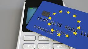 Payment or POS terminal with credit card featuring flag of the European Union. EU retail commerce or banking system. Plastic bank card featuring flag and POS Royalty Free Stock Images