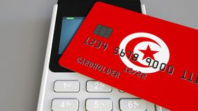 Payment or POS terminal with credit card featuring flag of Tunisia. Tunisian retail commerce or banking system. Plastic bank card featuring flag and POS terminal stock footage