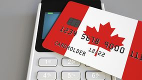 Payment or POS terminal with credit card featuring flag of Canada. Canadian retail commerce or banking system conceptual. Plastic bank card featuring flag and Stock Images
