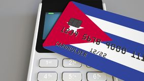Payment or POS terminal with credit card featuring flag of Cuba. Cuban retail commerce or banking system conceptual 3D. Plastic bank card featuring flag and POS Royalty Free Stock Images