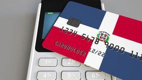 Payment or POS terminal with credit card featuring flag of the Dominican Republic. Retail commerce or banking system. Plastic bank card featuring flag and POS Royalty Free Stock Photography