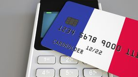 Payment or POS terminal with credit card featuring flag of France. French retail commerce or banking system conceptual. Plastic bank card featuring flag and POS Stock Photo
