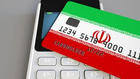 Payment or POS terminal with credit card featuring flag of Iran. Iranian retail commerce or banking system conceptual 3D. Plastic bank card featuring flag and Stock Photography