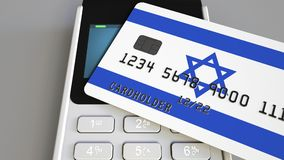 Payment or POS terminal with credit card featuring flag of Israel. Israeli retail commerce or banking system conceptual. Plastic bank card featuring flag and POS Stock Image