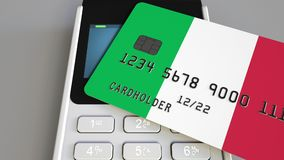 Payment or POS terminal with credit card featuring flag of Italy. Italian retail commerce or banking system conceptual. Plastic bank card featuring flag and POS Stock Image