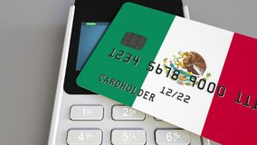 Payment or POS terminal with credit card featuring flag of Mexico. Mexican retail commerce or banking system conceptual. Plastic bank card featuring flag and POS Royalty Free Stock Image