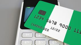 Payment or POS terminal with credit card featuring flag of Nigeria. Nigerian retail commerce or banking system. Plastic bank card featuring flag and POS terminal Stock Photo