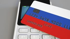Payment or POS terminal with credit card featuring flag of Russia. Russian retail commerce or banking system conceptual. Plastic bank card featuring flag and POS Royalty Free Stock Images