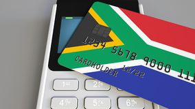 Payment or POS terminal with credit card featuring flag of South Africa. SAR retail commerce or banking system. Plastic bank card featuring flag and POS terminal stock illustration