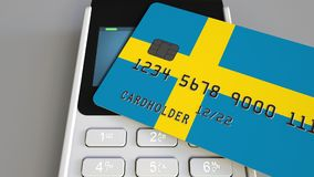 Payment or POS terminal with credit card featuring flag of Sweden. Swedish retail commerce or banking system conceptual. Plastic bank card featuring flag and POS Royalty Free Stock Image