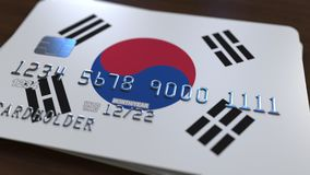 Plastic bank card featuring flag of South Korea. National banking system related 3D rendering. Plastic bank card featuring state flag Royalty Free Stock Image
