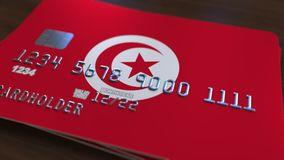 Plastic bank card featuring flag of Tunisia. National banking system related animation. Plastic bank card featuring state flag stock footage