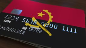 Plastic bank card featuring flag of Angola. Angolan national banking system related animation. Plastic bank card featuring state flag stock video