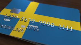Plastic bank card featuring flag of Sweden. National banking system related 3D rendering. Plastic bank card featuring state flag Royalty Free Stock Photo