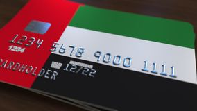 Plastic bank card featuring flag of the United Arab Emirates, UAE. National banking system related animation. Plastic bank card featuring state flag stock video