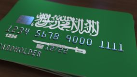 Plastic bank card featuring flag of Saudi Arabia. National banking system related 3D rendering. Plastic bank card featuring state flag Royalty Free Stock Image