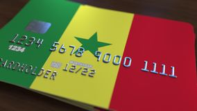 Plastic bank card featuring flag of Senegal. National banking system related 3D rendering. Plastic bank card featuring state flag Stock Photography