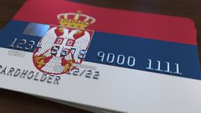 Plastic bank card featuring flag of Serbia. National banking system related 3D rendering. Plastic bank card featuring state flag Royalty Free Stock Photography
