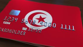 Plastic bank card featuring flag of Tunisia. National banking system related 3D rendering. Plastic bank card featuring state flag Stock Images