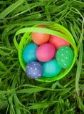 Plastic basket full of Easter eggs royalty free stock photos