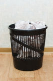 Plastic basket with garbage indoors Royalty Free Stock Photos