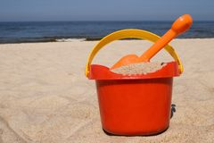 Plastic beach toys. Red plastic bucket and orange spade on the beach Royalty Free Stock Images