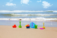 Plastic beach toys on beach with sea in background Stock Image