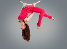 Plastic beautiful girl gymnast on acrobatic circus ring in flesh-colored suit. Stock Photos