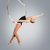 Plastic beautiful girl gymnast on acrobatic circus ring in flesh-colored suit Stock Images