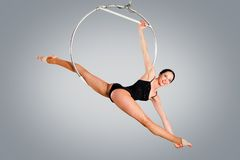 Plastic beautiful girl gymnast on acrobatic circus ring in flesh-colored suit Stock Photos