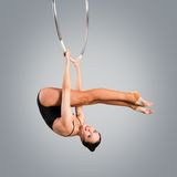 Plastic beautiful girl gymnast on acrobatic circus ring in flesh-colored suit Royalty Free Stock Photo