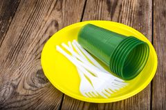 Plastic beschikbaar vaatwerk op houten lijst stock foto