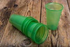 Plastic beschikbaar vaatwerk op houten lijst stock afbeelding