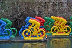 Plastic bikers on a river. Plastic colourful bikers in formation on a river Royalty Free Stock Photo