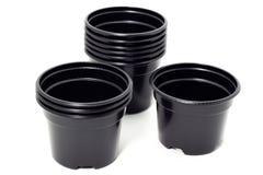 Plastic black flowerpots on white background Growing plant in black plastic flowerpot stock image