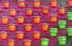 Plastic bloempotten op een bakstenen muurachtergrond stock afbeelding