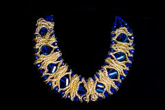 Plastic blue gold necklace. On a black background Royalty Free Stock Images