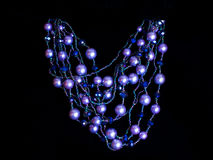 Plastic blue necklace. On a black background Royalty Free Stock Photos