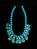 Plastic blue necklace. On a black background Royalty Free Stock Photography