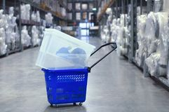Plastic blue trolley with the goods in the warehouse of store. Large stock of goods stock image