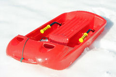 Plastic bob  for play and to descend from the mountains with. Red plastic bob for play and to descend from the mountains with snow Royalty Free Stock Image