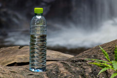 Plastic Bottle. Of Water placed on the log in Waterfall Area Stock Image